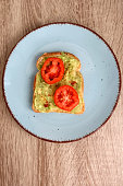 Toast with mashed avocado, cherry tomato and smoked pepper. Top view.