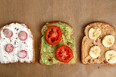 Three different toasts: cream cheese with radish and basil, avocado with cherry tomato and smoked paprika, peanut butter with banana and cinnamon. Top view, brown background.
