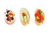 Toast sandwiches with avocado, tomatoes and olives. Isolated on white background. Top view