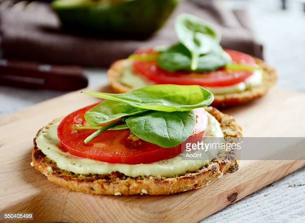 Toast with avocado sauce, tomato and baby spinach