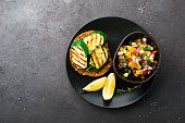 Toast with zucchini grill and salad of olives, cucumbers, tomato, sweet red onion, yellow chili pepper with grilled chicken breast. Top View