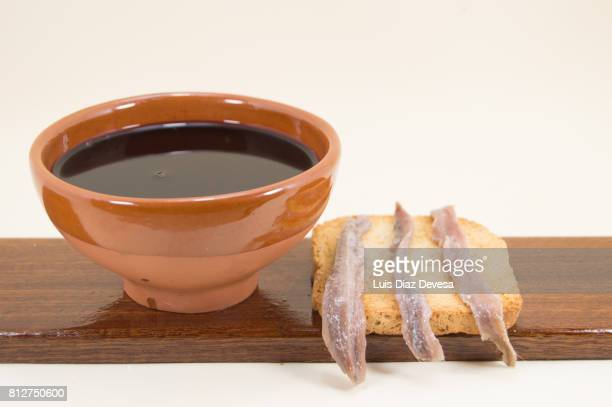 Toasted Bread with anchovies and an earthenware cup of red wine