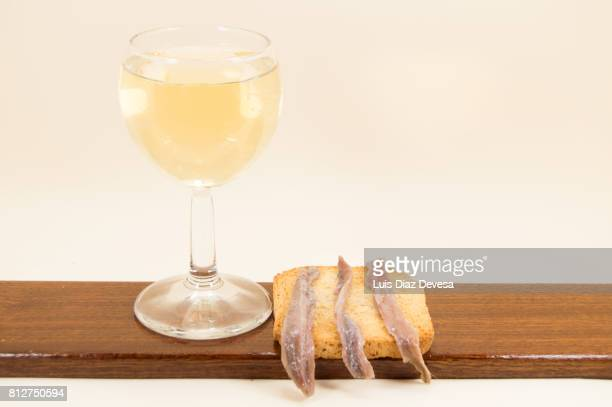 Toasted Bread with anchovies and cup white wine