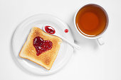 Toasted bread with raspberry jam in the shape of heart in plate and a cup of tea on white background, top view