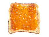 Slice of toasted bread with apricot jam isolated on a white background