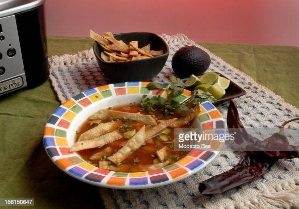 Toasted Guajillo chiles and roasted tomatillas flavor sopa Azteca or chicken soup with tortillas and avocado