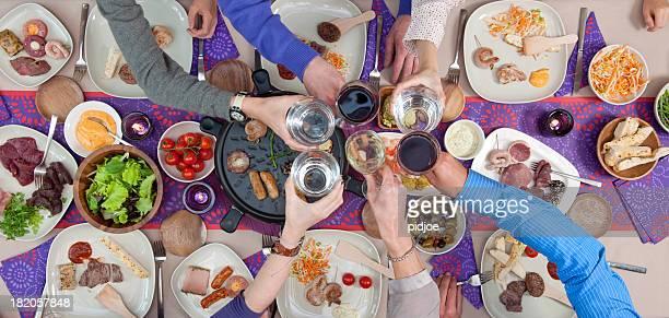 Anstoßen auf Esstisch mit gegrilltem Fleisch und Meeresfrüchte