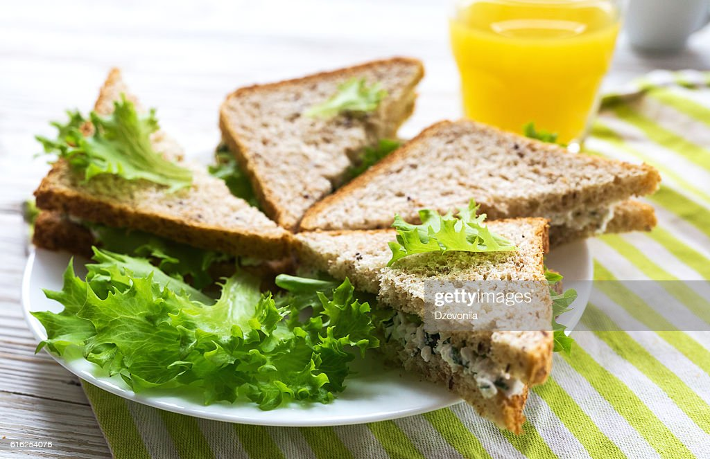 Toasts with cottage cheese and lettuce, and orange juice : Foto de stock