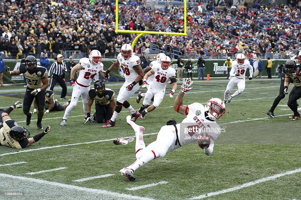 Tobais Palmer #4 of the North Carolina State Wolfpack gets tripped up on a kick return against the Vanderbilt Commodores during the Franklin American Mortgage Music City Bowl at LP Field on December 31, 2012 in Nashville, Tennessee.
