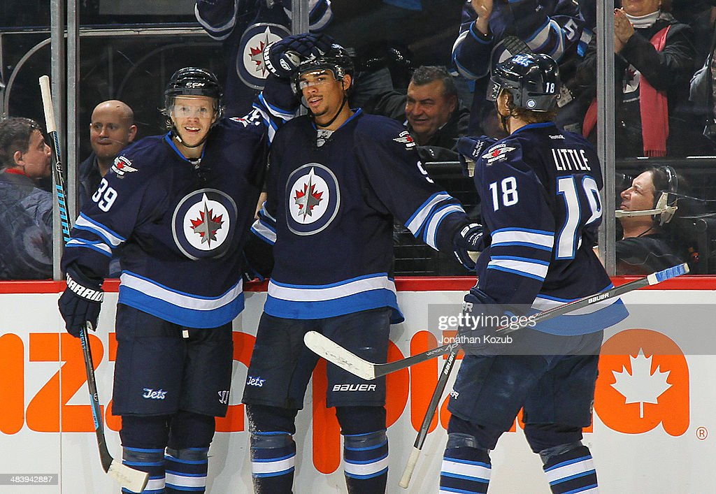 Tobias Enstrom #39, Evander Kane #9 and Bryan Little #18 of the Winnipeg Jets celebrate a third period goal against the Boston Bruins at the MTS Centre on April 10, 2014 in Winnipeg, Manitoba, Canada.