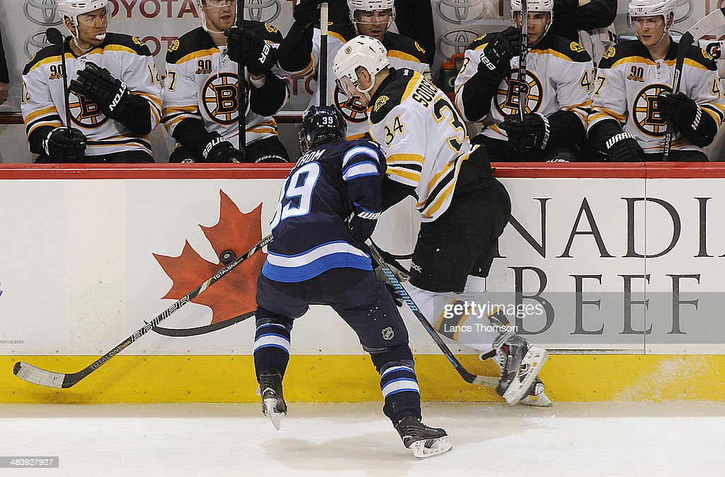 Tobias Enstrom #39 of the Winnipeg Jets and Carl Soderberg #34 of the Boston Bruins battle for the puck along the boards during second period action at the MTS Centre on April 10, 2014 in Winnipeg, Manitoba, Canada.