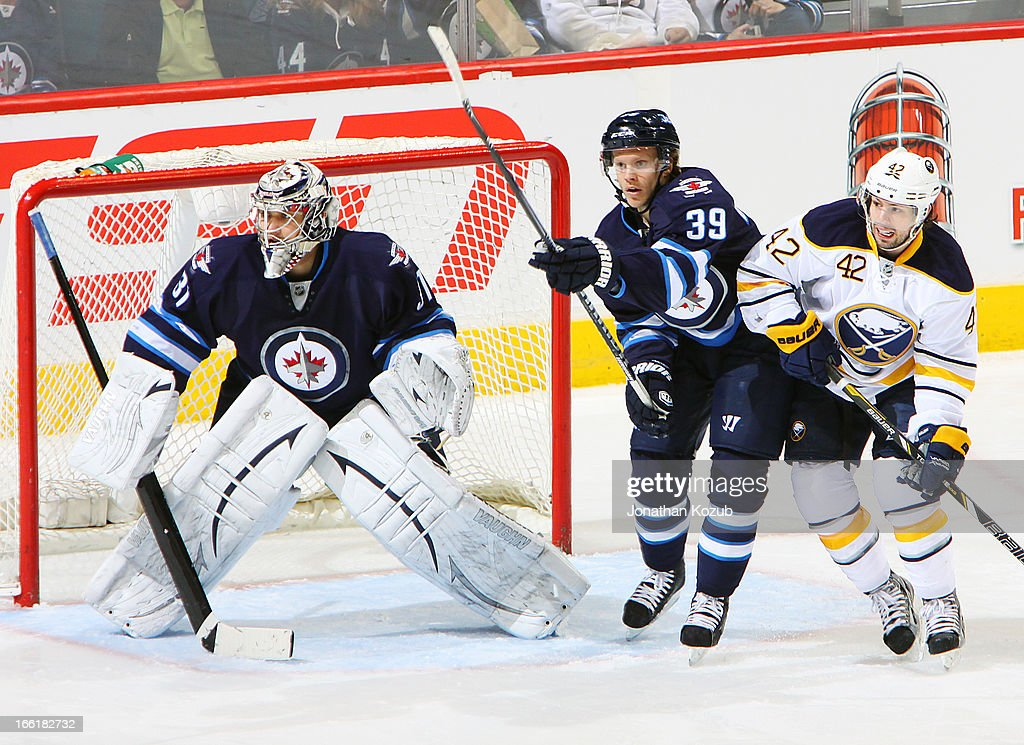 Tobias Enstrom #39 of the Winnipeg Jets battles Nathan Gerbe #42 of the Buffalo Sabres in the crease as goaltender Ondrej Pavelec #31 keeps an eye on the play during first-period action at the MTS Centre on April 9, 2013 in Winnipeg, Manitoba, Canada.