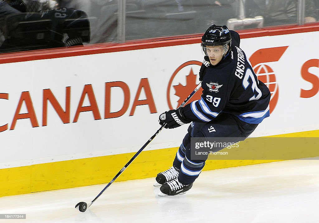 Tobias Enstrom #39 of the Winnipeg Jets carries the puck around the boards during second period action against the Dallas Stars at the MTS Centre on October 11, 2013 in Winnipeg, Manitoba, Canada.