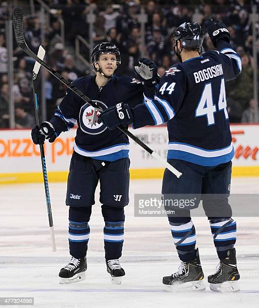 Tobias Enstrom of the Winnipeg Jets is congratulated for his goal by teammate Zach Bogosian in second period action in an NHL game against the Ottawa...