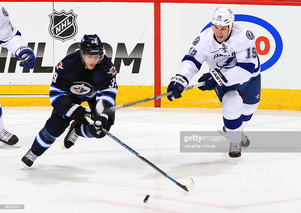 Tobias Enstrom #39 of the Winnipeg Jets plays the loose puck as B.J. Crombeen #19 of the Tampa Bay Lightning gives chase during second period action at the MTS Centre on January 7, 2014 in Winnipeg, Manitoba, Canada.