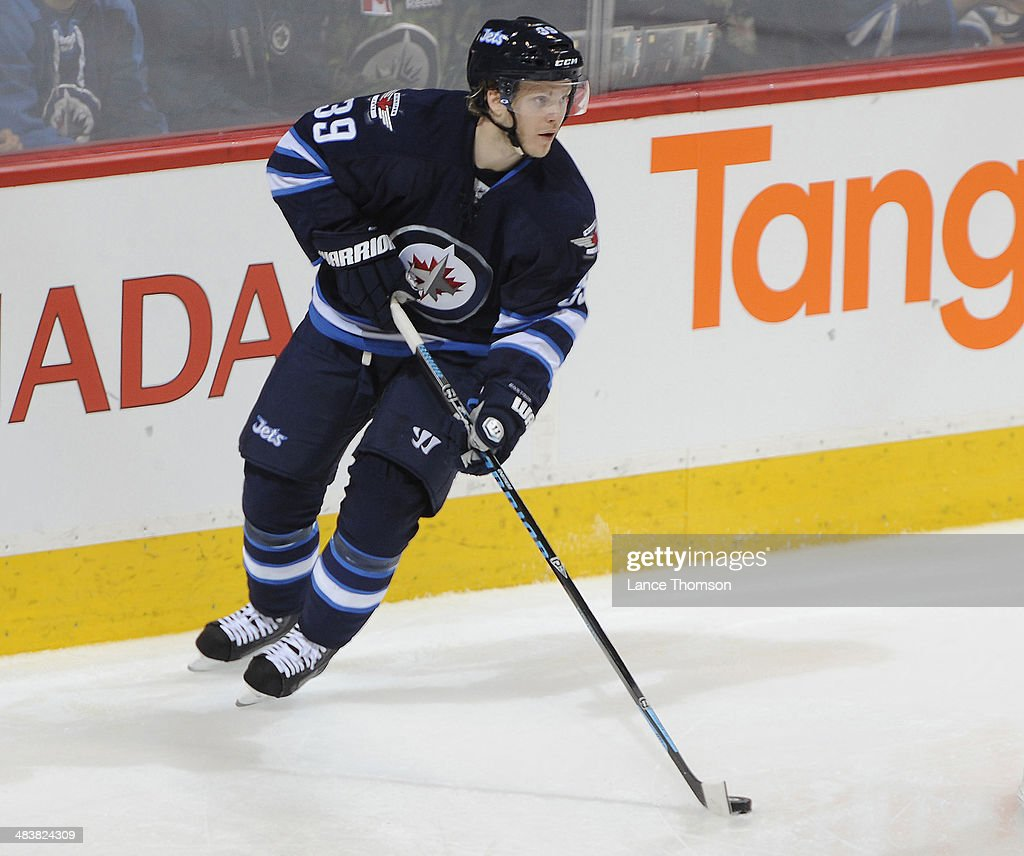Tobias Enstrom #39 of the Winnipeg Jets plays the puck up the ice during second period action against the Minnesota Wild at the MTS Centre on April 7, 2014 in Winnipeg, Manitoba, Canada. The Wild defeated the Jets 1-0.