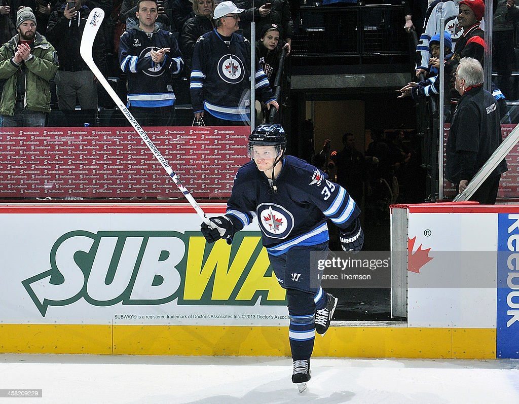 <a gi-track='captionPersonalityLinkClicked' href=/galleries/search?phrase=Tobias+Enstrom&family=editorial&specificpeople=2538468 ng-click='$event.stopPropagation()'>Tobias Enstrom</a> #39 of the Winnipeg Jets raises his stick in salute after receiving second star honors following a 5-2 victory over the Florida Panthers at the MTS Centre on December 20, 2013 in Winnipeg, Manitoba, Canada.