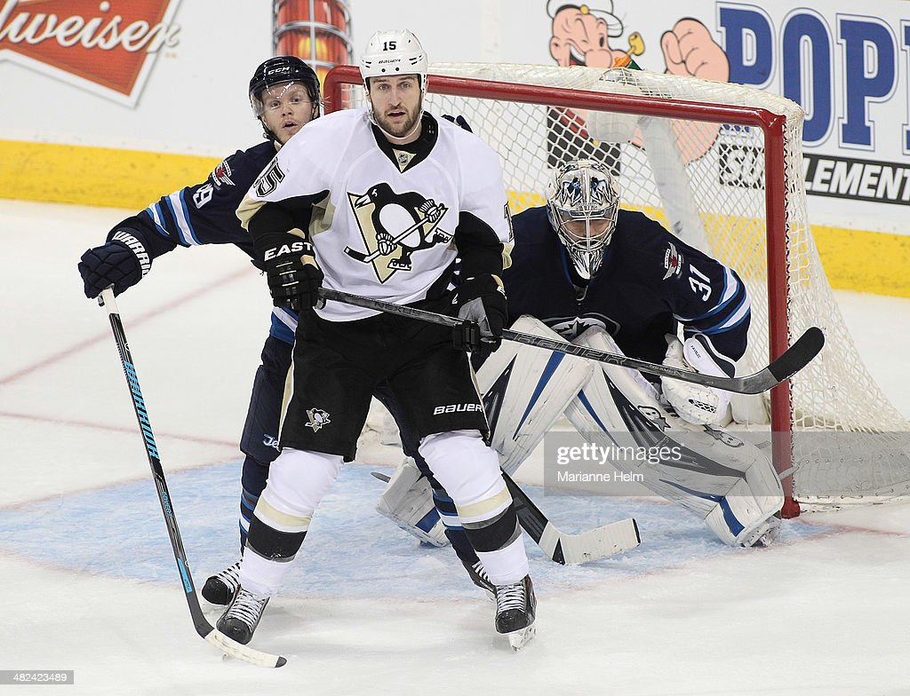 <a gi-track='captionPersonalityLinkClicked' href=/galleries/search?phrase=Tobias+Enstrom&family=editorial&specificpeople=2538468 ng-click='$event.stopPropagation()'>Tobias Enstrom</a> #39 of the Winnipeg Jets tries to look around <a gi-track='captionPersonalityLinkClicked' href=/galleries/search?phrase=Tanner+Glass&family=editorial&specificpeople=4596666 ng-click='$event.stopPropagation()'>Tanner Glass</a> #15 of the Pittsburgh Penguins as goaltender Ondrej Pavelec #31 protects his net in third period action in an NHL game at the MTS Centre on April 3, 2014 in Winnipeg, Manitoba, Canada.