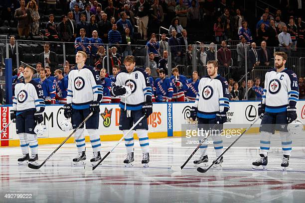 Tobias Enstrom Tyler Myers Blake Wheeler Bryan Little and Andrew Ladd of the Winnipeg Jets look on during the singing of the national anthem before...