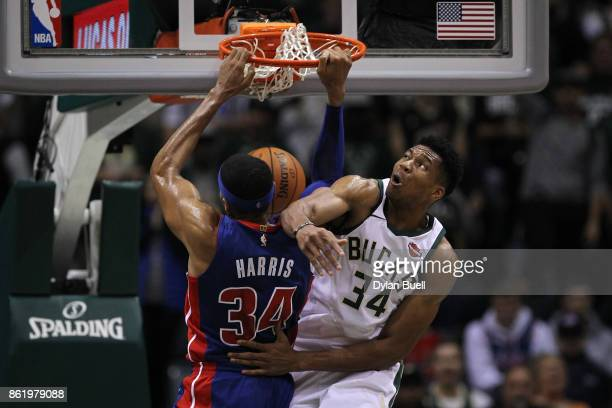 Tobias Harris of the Detroit Pistons dunks the ball past Giannis Antetokounmpo of the Milwaukee Bucks in the second quarter during a preseason game...