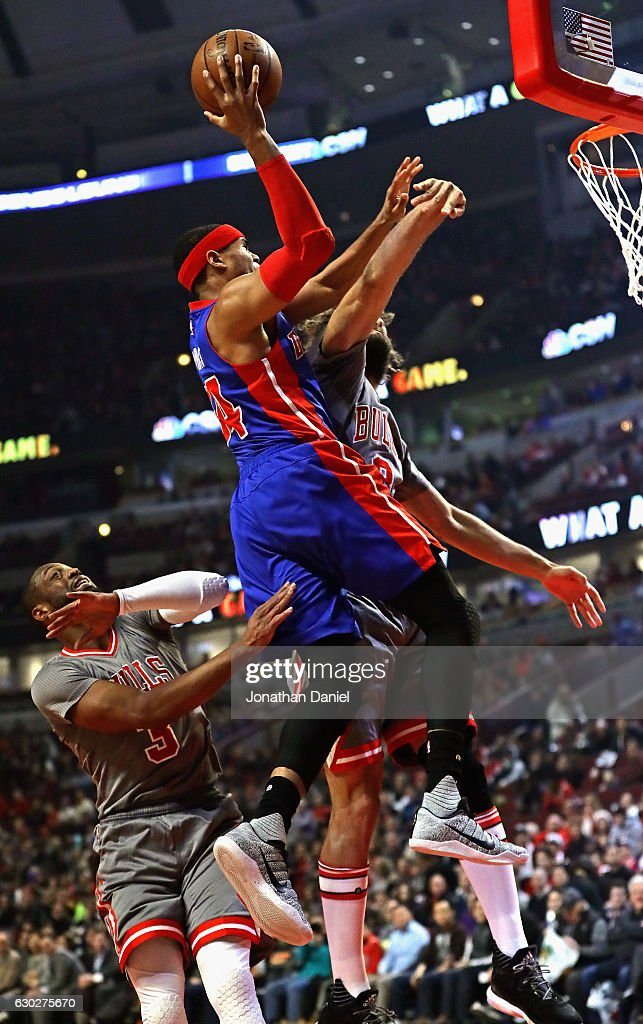 Tobias Harris #34 of the Detroit Pistons goes up for a shot over Dwyane Wade #3 and Robin Lopez #8 of the Chicago Bulls at the United Center on December 19, 2016 in Chicago, Illinois.