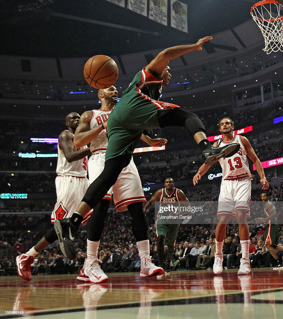 Tobias Harris #15 of the Milwaukee Bucks looses control of the ball after being fouled by Carlos Boozer #5 of the Chicago Bulls at the United Center on November 26, 2012 in Chicago, Illinois.