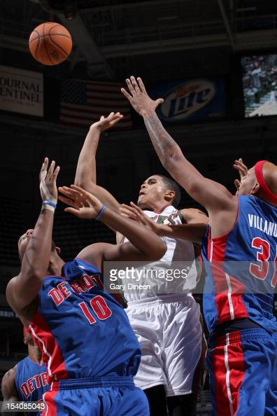 Tobias Harris of the Milwaukee Bucks shoots against Greg Monroe and Charlie Villanueva of the Detroit Pistons during the NBA preseason game on...