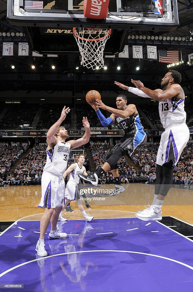 Tobias Harris of the Orlando Magic passes against Aaron Gray and Derrick Williams of the Sacramento Kings on January 10 2014 at Sleep Train Arena in...