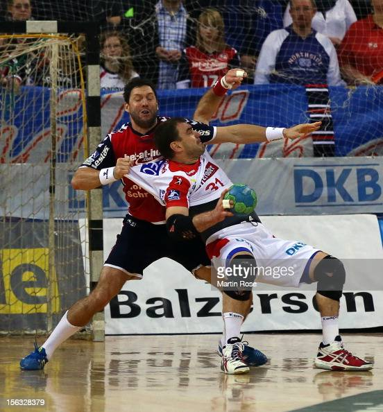 Tobias Karlsson of Flensburg is challenged by Jurecki Bartosz of Magdeburg during the DKB Handball Bundesliga match between SG FlensburgHandewitt and...