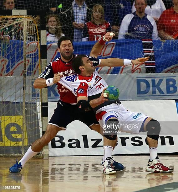 Tobias Karlsson of Flensburg is challenged by Jurecki Bartosz of Magdeburg during the DKB Handball Bundesliga match between SG FlensburgHandewitt and...