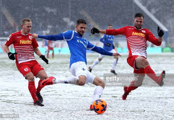 Tobias Kempe of Darmstadt and Alexander Nandzik and Benedikt Gimber of Regensburg battle for the ball during the Second Bundesliga match between SV...