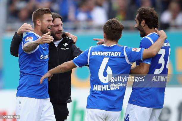 Tobias Kempe of Darmstadt celebrates his team's first goal with team mates Marvin Mehlem and Hamit Altintop and head coach Torsten Frings during the...