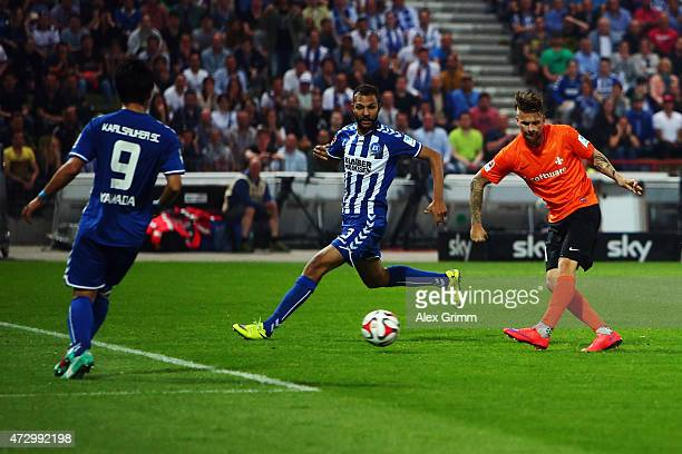 Tobias Kempe of Darmstadt scores his team's first goal against Daniel Gordon and Hiroki Yamada of Karlsruhe during the Second Bundesliga match...
