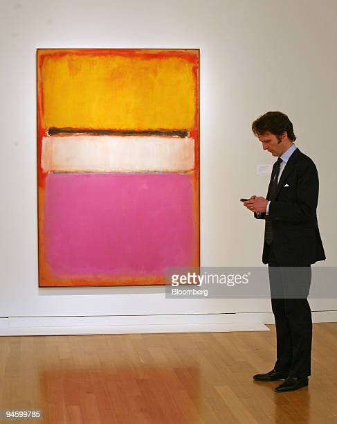 Tobias Meyer global head of contemporary art for Sotheby's works on his PDA while standing beside Mark Rothko's 'White Center ' at Sotheby's on...