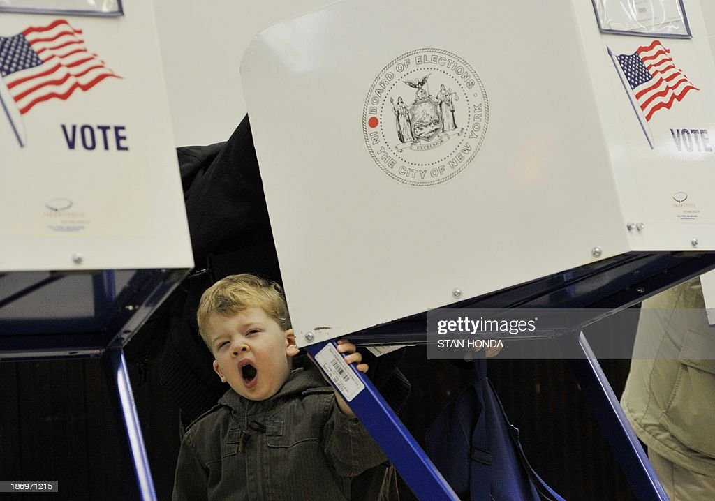 Tobias Nichols, 2 years old, yawns as his father Dan votes at the Park Slope Branch Public Library in the Brooklyn borough of New York November 5, 2013. AFP PHOTO/Stan HONDA