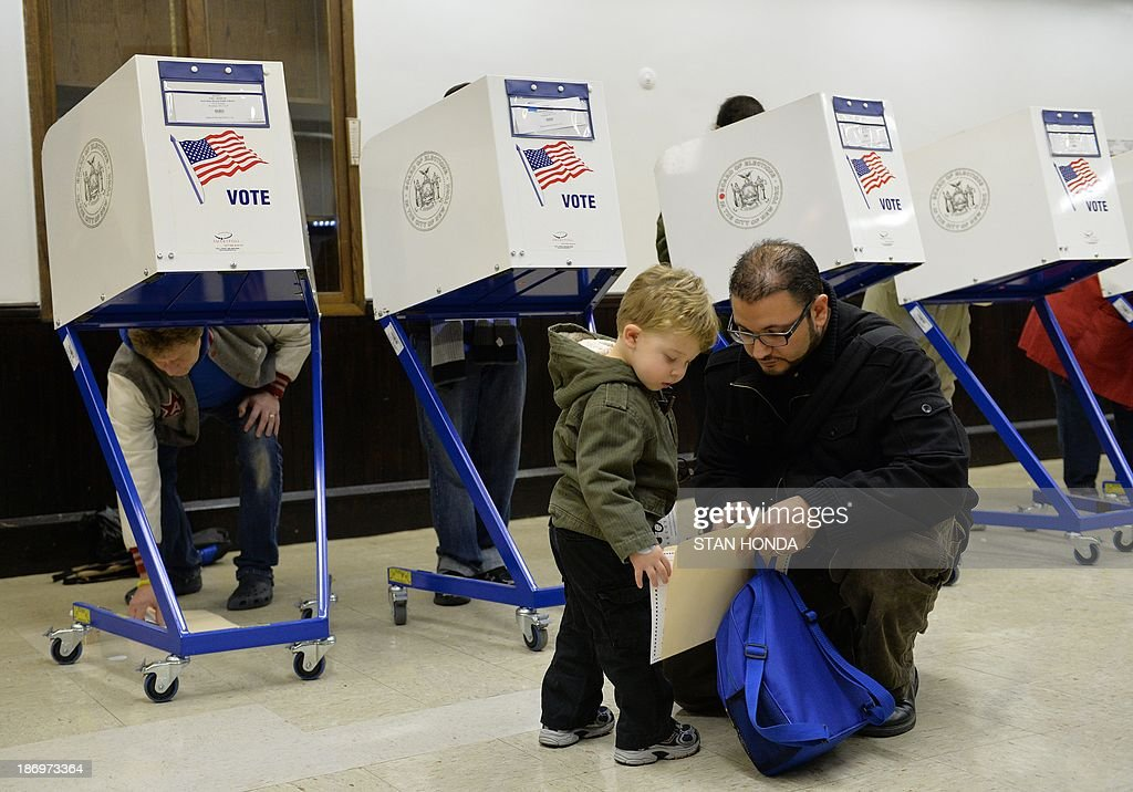 Tobias Nichols, 2, and his father Dan hold a ballot before voting at the Park Slope Branch Public Library in the Brooklyn borough of New York November 5, 2013. AFP PHOTO/Stan HONDA