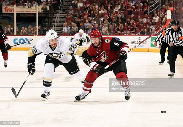 Tobias Rieder of the Arizona Coyotes pushes the puck up ice in front of Ian Cole of the Pittsburgh Penguins during the second period at Gila River...