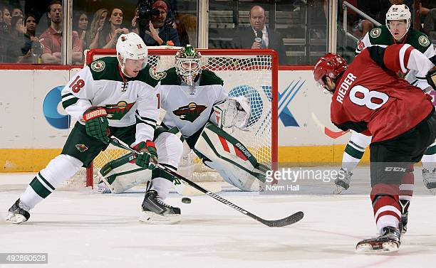 Tobias Rieder of the Arizona Coyotes shoots the puck toward goaltender Devan Dubnyk and Ryan Carter of the Minnesota Wild during the first period at...