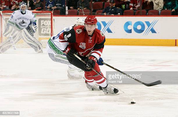 Tobias Rieder of the Arizona Coyotes skates with the puck ahead of Christopher Tanev of the Vancouver Canucks during the second period at Gila River...