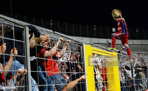Tobias Schweinsteiger of Bayern Muenchen stands on the fence in front of the Bayern Muenchen fans and celebrates his teams victory in the...