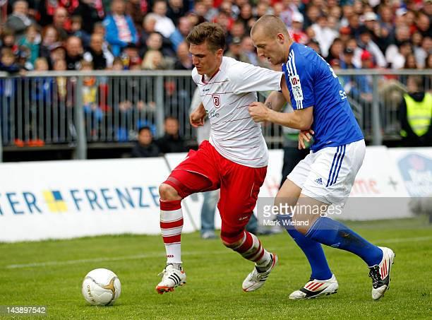 Tobias Schweinsteiger of Jahn Regensburg is challenged by Ralf Schmidt of CZ Jena during the Third League match between Jahn Regensburg and CZ Jena...