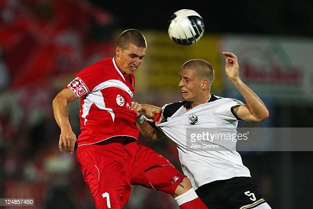 Tobias Schweinsteiger of Regensburg jumps for a header with Daniel Schulz of Regensburg during the Third League match between SV Sandhausen and Jahn...