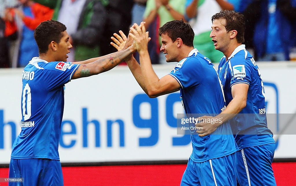 Tobias Strobl (C) of Hoffenheim celebrates his team's third goal with team mates <a gi-track='captionPersonalityLinkClicked' href=/galleries/search?phrase=Roberto+Firmino+-+Soccer+Player&family=editorial&specificpeople=7522629 ng-click='$event.stopPropagation()'>Roberto Firmino</a> (L) and David Abraham during the Bundesliga match between 1899 Hoffenheim and SC Freiburg at Wirsol Rhein-Neckar-Arena on August 24, 2013 in Sinsheim, Germany.