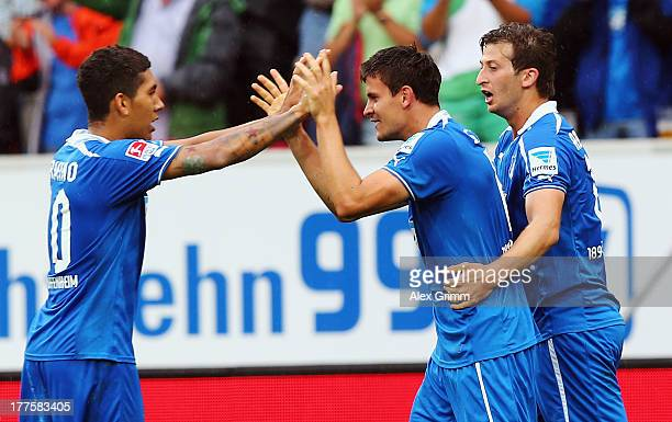 Tobias Strobl of Hoffenheim celebrates his team's third goal with team mates Roberto Firmino and David Abraham during the Bundesliga match between...