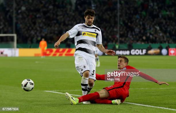 Tobias Strobl of Moenchengladbach and Bastian Oczipka of Frankfurt battle for the ball during the DFB Cup semi final match between Borussia...