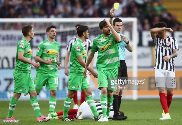 Tobias Strobl of Moenchengladbach reacts as referee Harm Osmers shows him the yellow card during the Bundesliga match between Eintracht Frankfurt and...