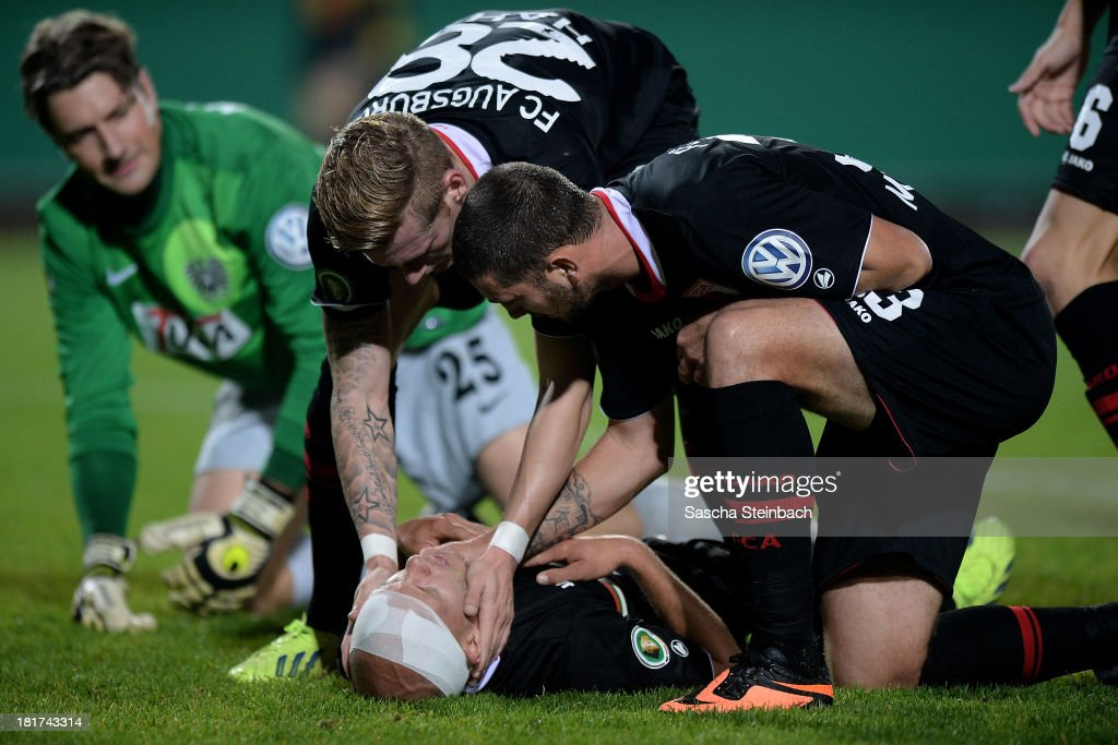 Tobias Werner of Augsburg lies on the pitch after picking up an injury while scoring their opening goal during DFB Cup second round match between Preussen Muenster and FC Augsburg at Preussenstadion on September 24, 2013 in Muenster, Germany.