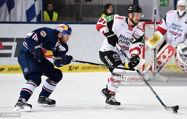 Tobias Woerle of EHC Red Bull Muenchen and Moritz Mueller of the Koelner Haien during the game between the EHC Red Bull Muenchen and Koelner Haie on...