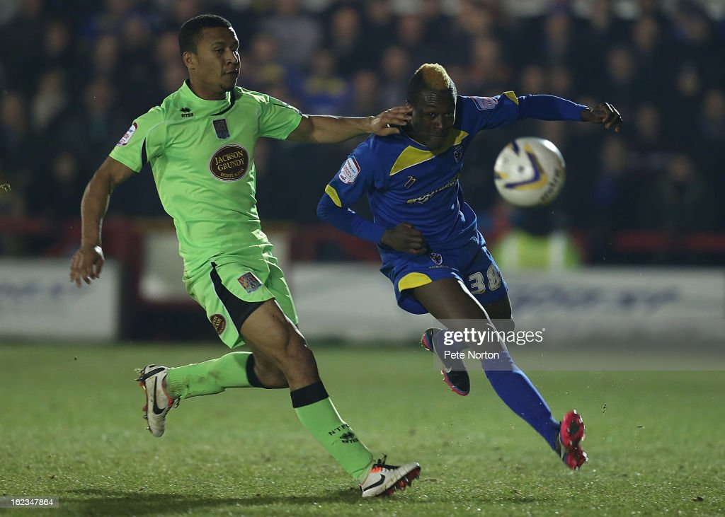Toby Ajala of AFC Wimbledon plays the ball under pressure from Joe Widdowson of Northampton Town during the npower League Two match between AFC Wimbledon and Northampton Town at The Cherry Red Records Stadium on February 19, 2013 in Kingston upon Thames, England.