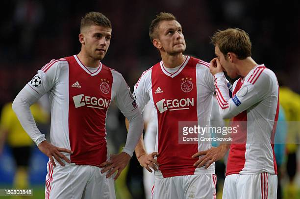 Toby Alderweireld of Amsterdam and teammates Siem de Jong and Christian Eriksen look dejected after the UEFA Champions League Group D match between...